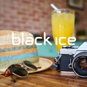 Black Ice sunglasses and hat sit on a table with camera and juice