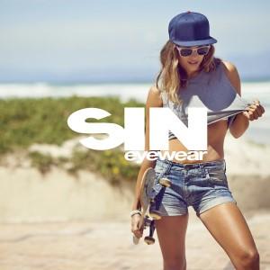 SIN Eyewear girl with skateboard stands on beachfront wearing SIN sunnies