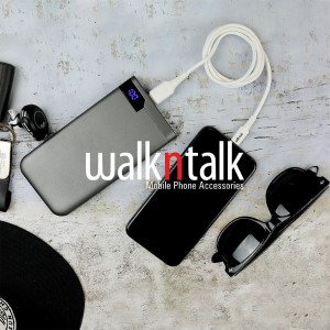 WalknTalk mobile phone powerbank and cable on concrete background with sunglasses and keys